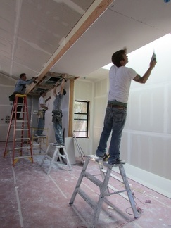 Working together on the final pieces of sheetrock