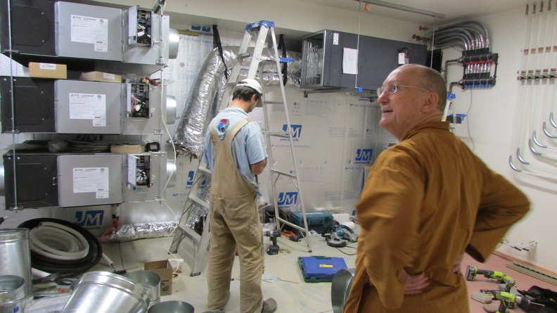 Ajahn Pasanno inspects the mechanical room