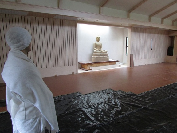 Cork flooring being installed.  Anagarika Dorian using the hall for walking meditation.