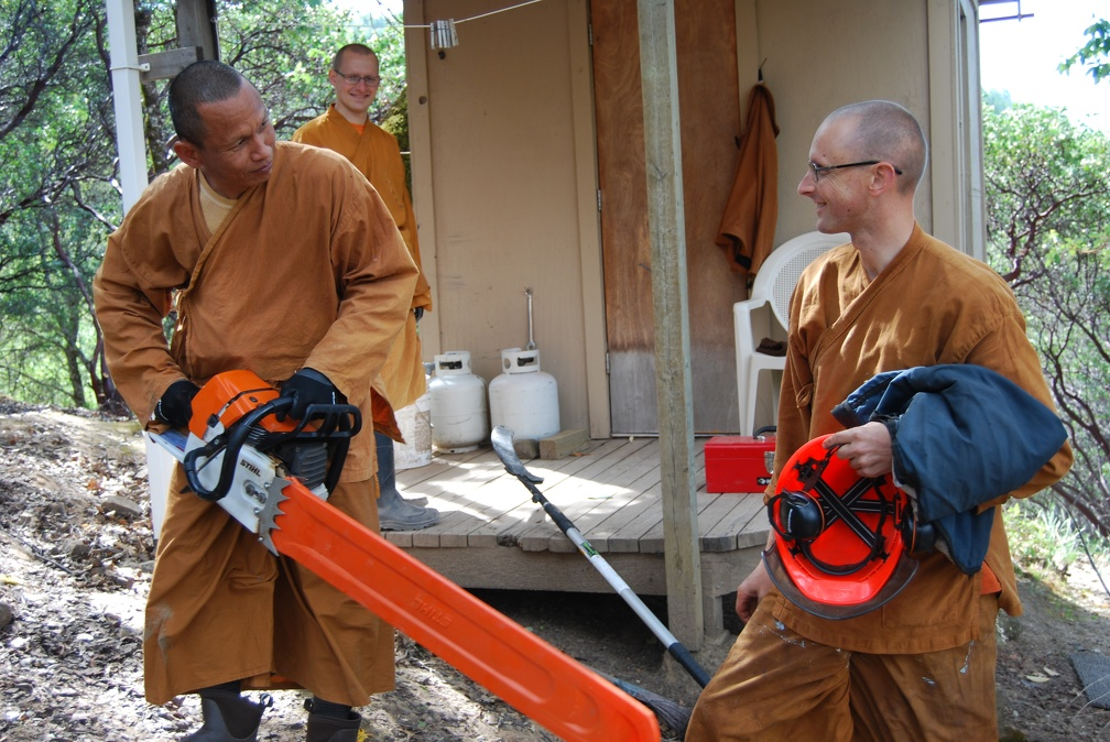 Ajahn Ñaniko and Ajahn Sek inspect the chainsaw as Sāmaṇera Cittapālo looks on.