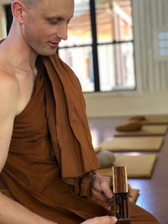Ajahn Nyaniko offers a home-made sewing kit to the visiting monks