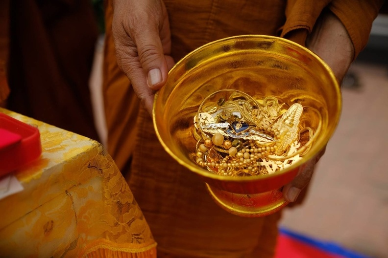 Gifts of the faithful to be melted into the flame crowing a new Buddha Image