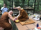Ajahn Jayasaro paying respects to Luang Por Pasanno on his birthday outside of his cave retreat.