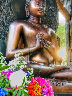 The Buddha Image at the monastery's outdoor meditation platform, honored at sunset with bouquets of flowers.