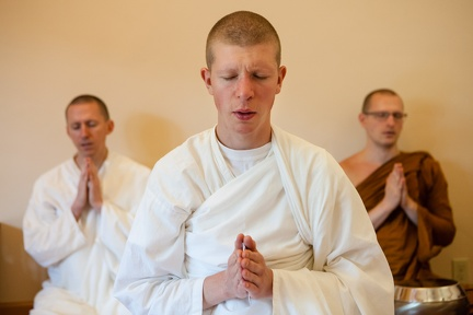A new monastic postulant gives a blessing before the meal