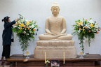 A lay guest decorates the sandstone Buddha with fresh flowers.