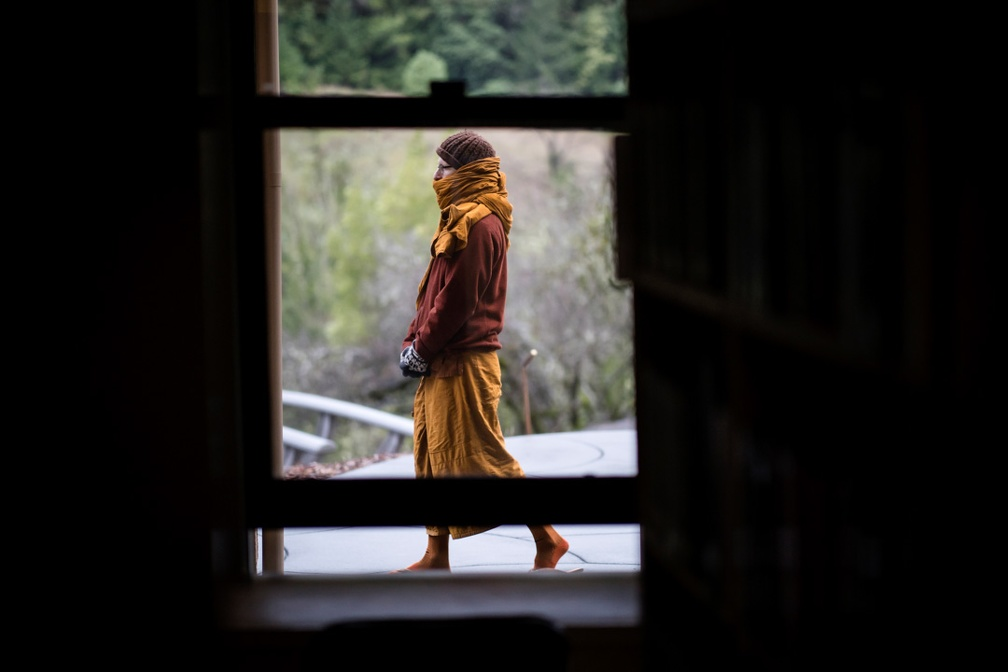A sāmaṇera bundles up against the cold as he does walking meditaiton outside the library window.