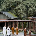 Monks walking to the meal during a drizzle.