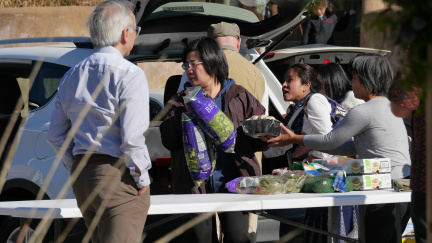 Volunteers help to organize food offerings