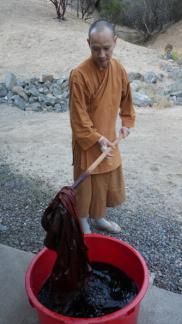 Ajahn Kassapo stirring the dye bath
