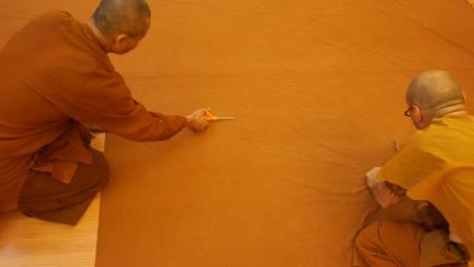 After drawing out the pattern Ajahn Sek and Tan Rakkhito cut the Kathina cloth to prepare for sewing