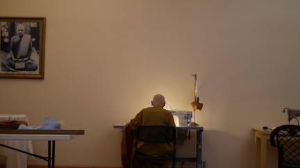 Ajahn Karuṇadhammo sewing the corners of the Kathina robe