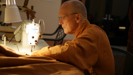 Luang Por Pasanno sewing on the boarder of the Kathina robe