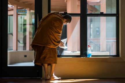 Bhikkhu Gunaviro cleans the Dhamma Hall before a full-moon lunar observance day in early April.