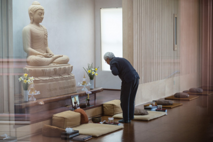 Jeed pauses to pay homage to the Buddharupa while arranging flowers in the Dhamma hall.