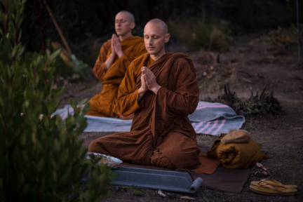Ajahn Ñaniko leads chanting during an evening puja at the future chedi site, located above the Cool Oaks trail.