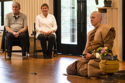 With his head freshly-shaved and robes newly-dyed, Dhammavaro prepares to approach his Preceptor with his requisites and an offering of gifts while his parents Don and Terri look on.