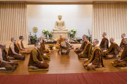 Dressed in his triple robe set, Dhammavaro, center, receives his monk ordination from Luang Por Pasanno in the presence of the Abhayagiri monastic community on May 17, 2020.