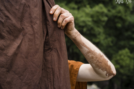 Dye drips from Dhammavavro's arm as he hangs his jiworn from a clothesline outside the monks' utility building.