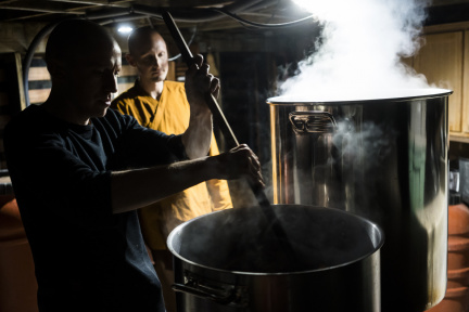 Dhammavavro stirs madrone bark in the steeping pot as Ajahn Ñaniko looks on.