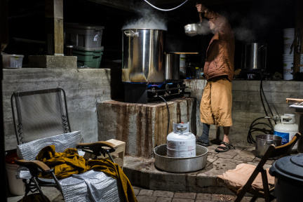 After straining the madrone bark, Dhammavavro moves the weak dye liquid to another pot, where it will be boiled and reduced. To stay on schedule, he spent four nights' vigil in a cold basement retrofitted with dyeing equipment.