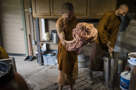 Dhammavavro applies mortant to a robe alongside Ajahn Ñaniko, the abbot of Abhayagiri, who dyed a robe at the same time. It's common for a novice to have dedicated help through this process from a more senior monk.