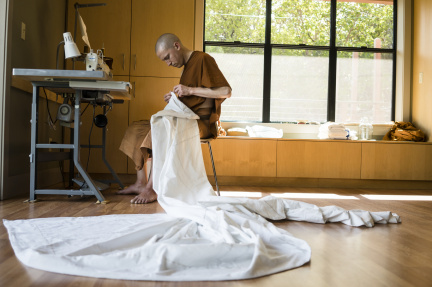 "After daily chores and the midday meal, Dhammavaro sews his three robes. The ""triple set""consists of the sabong - a robe worn at the waist; the jiworn - an outer robe covering the body; and the sanghati - a double-layered robe for formal occasions."