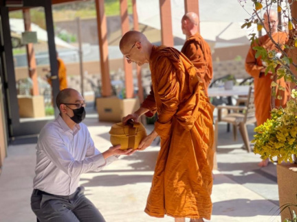 Ajahn Karunadhammo hands his bowl to a visitor