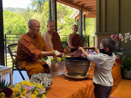 Luang Por has his hands cleansed by a visitor