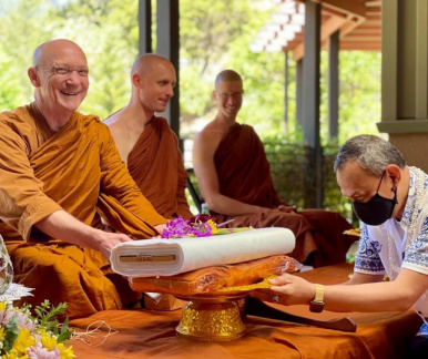 Luang Por receives cloth from a donor